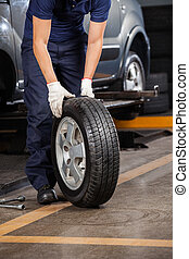 Mechanic Holding Car Tire At Garage