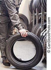 Mechanic holding car tire at warehouse.