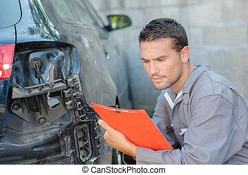 Mechanic holding clipboard assessing car