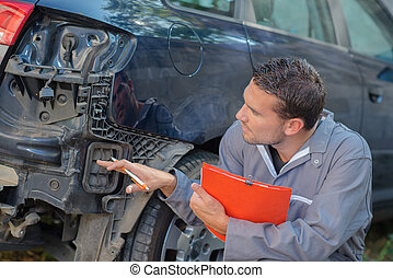 Mechanic holding clipboard assessing car