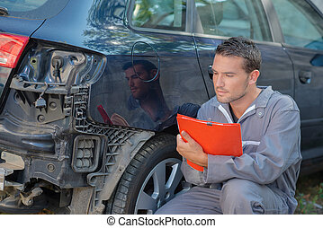 Mechanic holding clipboard, looking at damage to rear of car