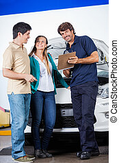 Mechanic Holding Clipboard While Standing With Couple