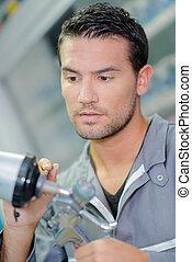 Mechanic holding components of spray gun