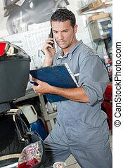 mechanic holding folder, on telephone