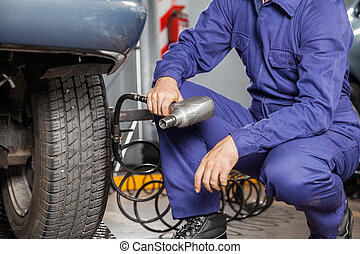 Mechanic Holding Pneumatic Wrench By Car - Midsection of...