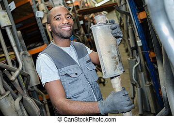 mechanic holding spare parts exhaust pipe