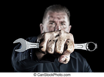 Mechanic holding wrench - A mechanic covered in grime and ...