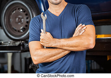 Mechanic Holding Wrench In Repair Shop