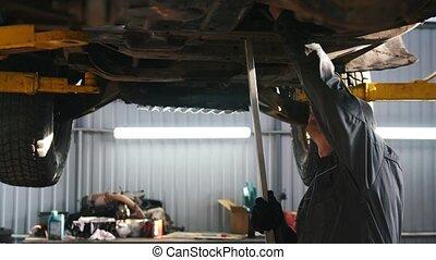 Mechanic in car service checks the auto's bottom for luxury SUV - slider shot
