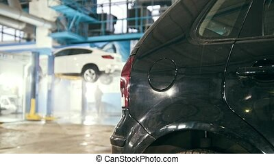 Mechanic in car service is washing luxury SUV under bottom...