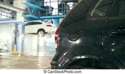 Mechanic in car service is washing luxury SUV under bottom...