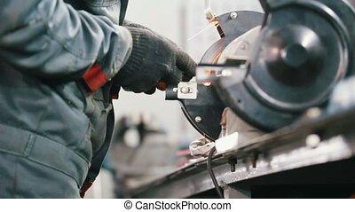 Mechanic in car service mechanic sharpens the detail on the sandpaper