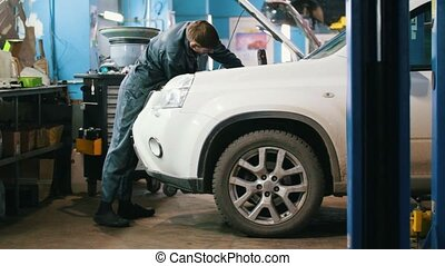 Mechanic in car service - repairing for white SUV, wide...