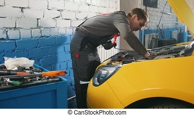 Mechanic in car service - repairing in engine compartment