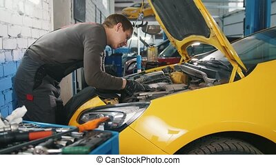 Mechanic in car service - repairing in engine compartment,...