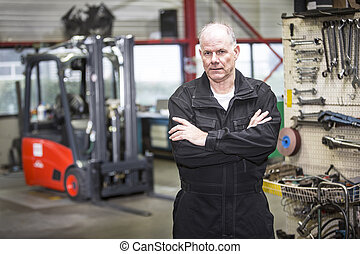 mechanic in forklift garage - middle aged mechanic standing...