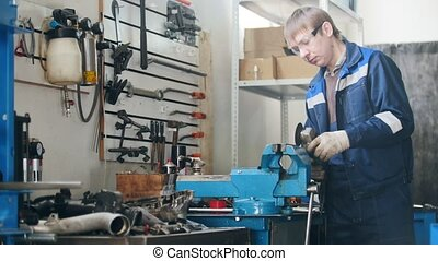 Mechanic in garage at work - circular saw sparkles during worker grinding metal detail hamstrung automobile repairing