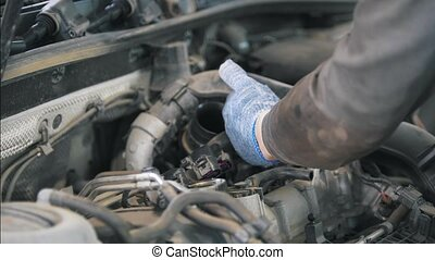 Mechanic in gloves establishing auto parts on the car
