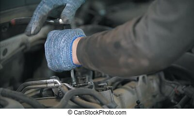 Mechanic in gloves with wrench dismantle the car