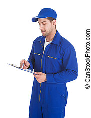 Mechanic In Overall Writing On Clipboard - Young male...