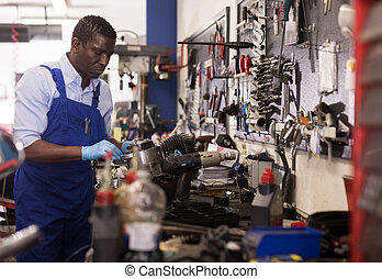 Mechanic in overalls repairing a motorcycle engine in a garage