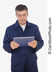 Mature mechanic in uniform using digital tablet over white background