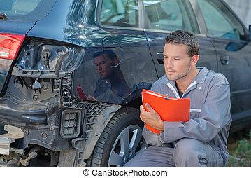 Mechanic inspecting a damaged car
