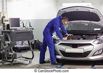 Mechanic leaning on a car looking at the engine in a garage
