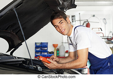mechanic leaning on bonnet with tester equipment and looking...