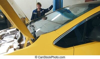 Mechanic lifts yellow car in garage automobile service - small business