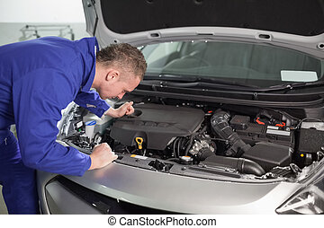 Mechanic looking at an engine of car in a garage