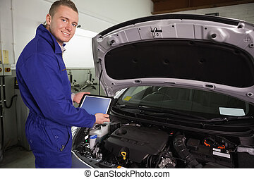 Mechanic looking at camera while holding a tablet computer
