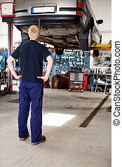 Mechanic Looking at Car - A young mechanic looking at a car...