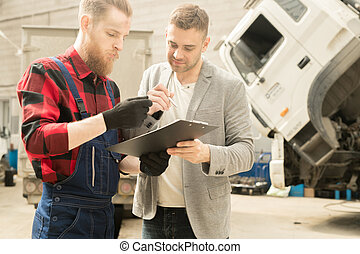 Mechanic Looking At Checklist With Client