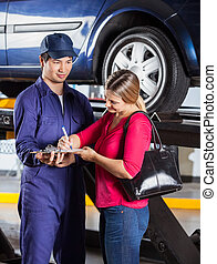 Mechanic Looking At Customer Signing Document