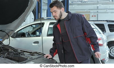 Mechanic looks under the car hood at the car service