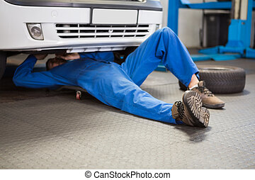 Mechanic lying and working under car