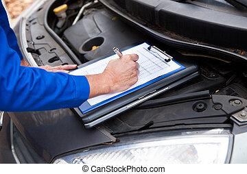 Mechanic Maintaining Car Records - Close-up Of A Mature...