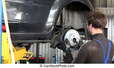 Mechanic man add new brake disk to old rusty car.