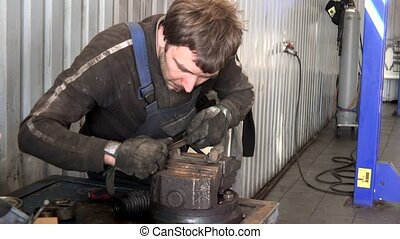 mechanic man grind rusty metal with rasp tool in garage.