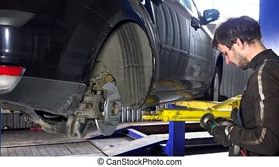 Mechanic man grinding rusty bolts with electric grinder tool near lifted car
