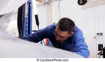mechanic man repairing car at workshop - car service,...