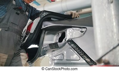 Mechanic man repairs the car body with a hammer in a car repair shop
