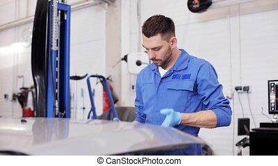 mechanic man with lamp repairing car at workshop 19