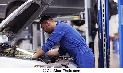 mechanic man with lamp repairing car at workshop 42