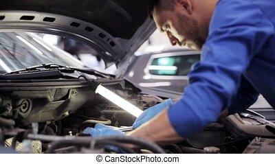 mechanic man with lamp repairing car at workshop 5