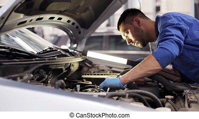 mechanic man with lamp repairing car at workshop 7