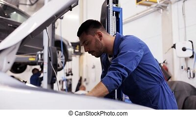 mechanic man with lamp repairing car at workshop - car...
