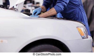 mechanic man with wrench repairing car at workshop 31 - car...