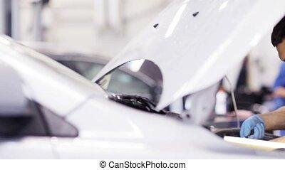 mechanic man with wrench repairing car at workshop 52 - car...
